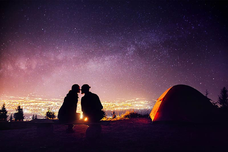 Happy couple in silhouette kissing near campfire and orange tent
