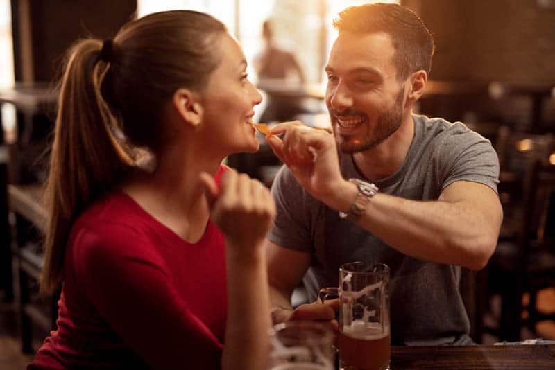 Happy man feeding his girlfriend with nacho chips while drinking beer together in a pub
