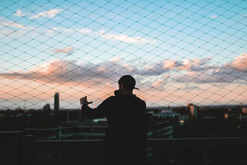 silhouette of man looking at city