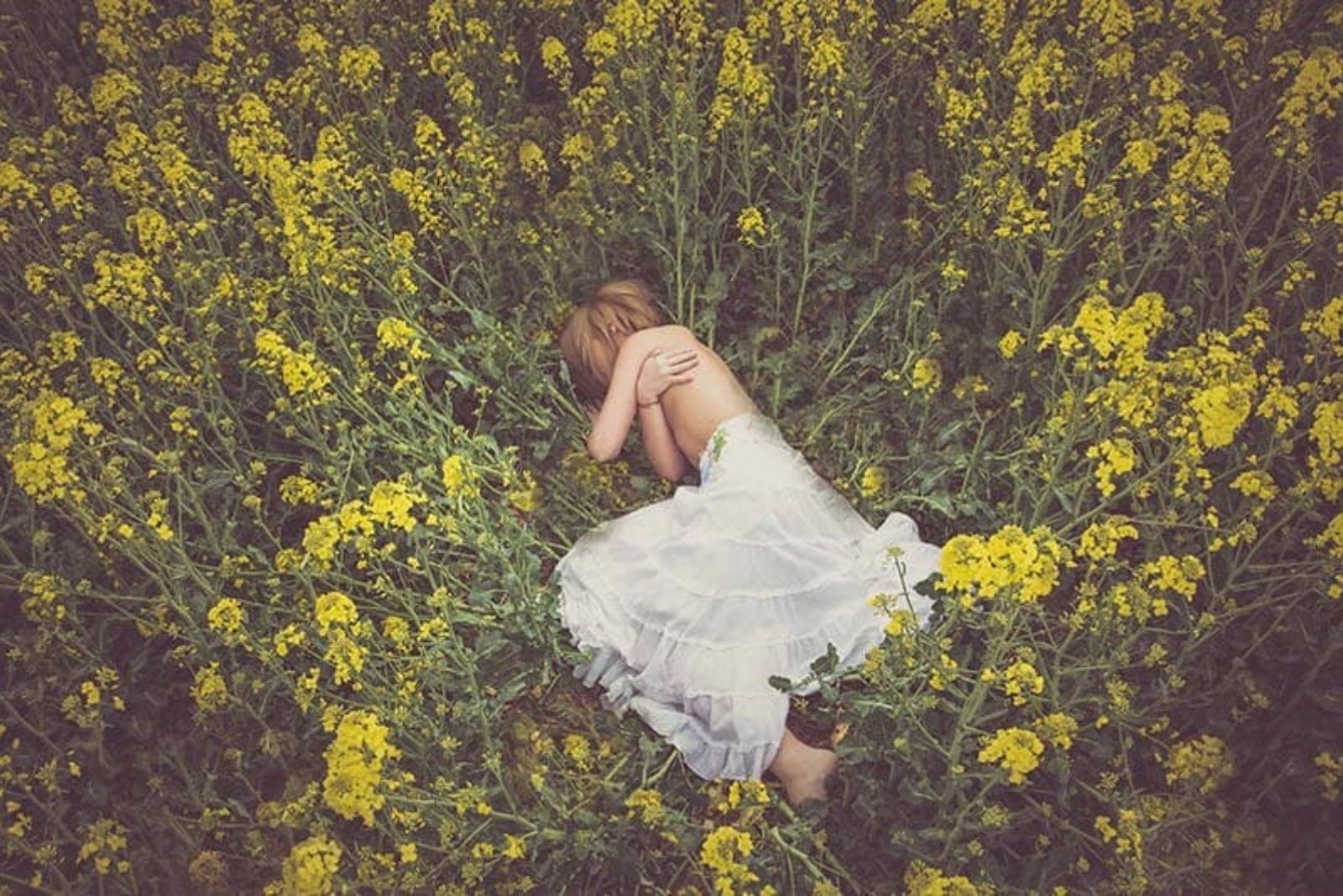 the woman lies in a field of flowers