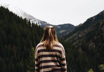 back view of blonde girl wearing long sleeve shirt and standing in front of mountains