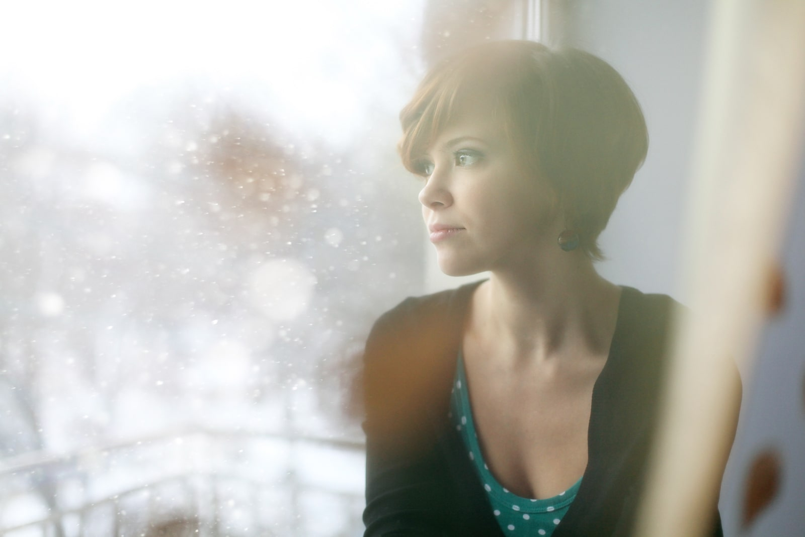 a sad short-haired brunette stands by the window and watches the snow fall outside