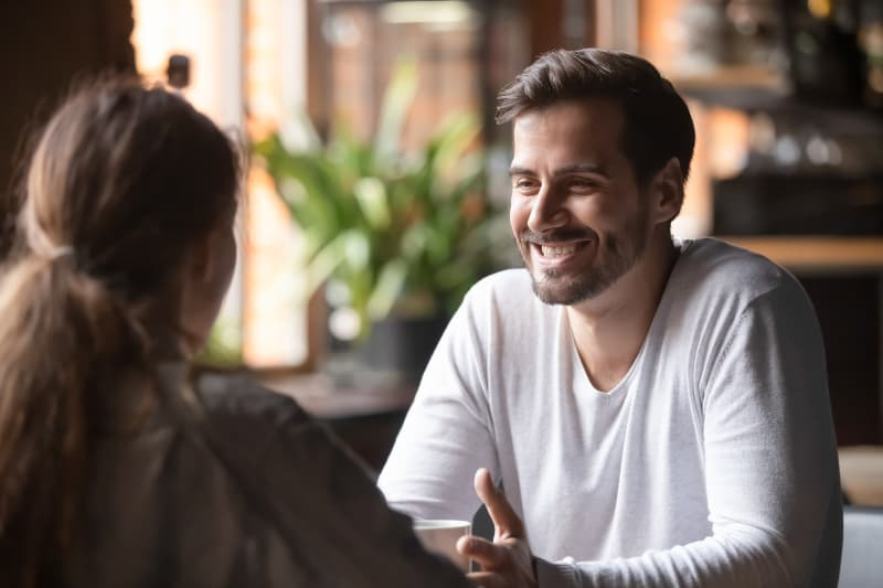 smiling man looking at woman in cafe