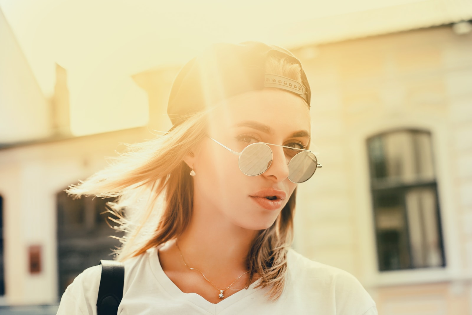 a portrait of a beautiful girl with a cap and sunglasses