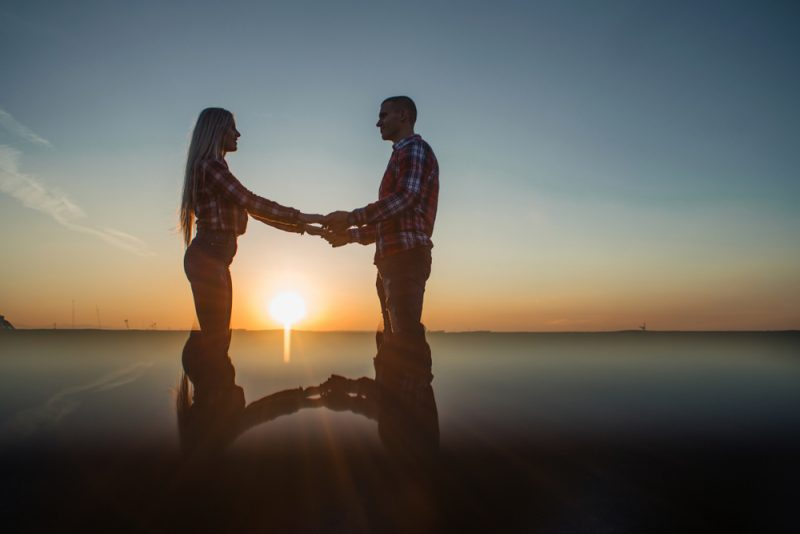 The lovely couple in love standing on the roof