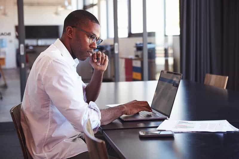Young black man in wearing glasses using laptop in office