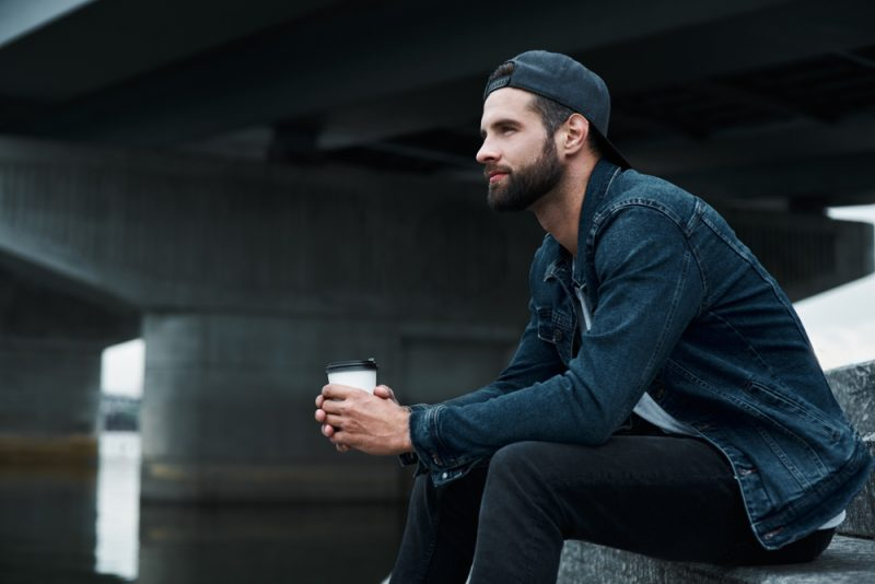 Young stylish man sitting on stairs on city street