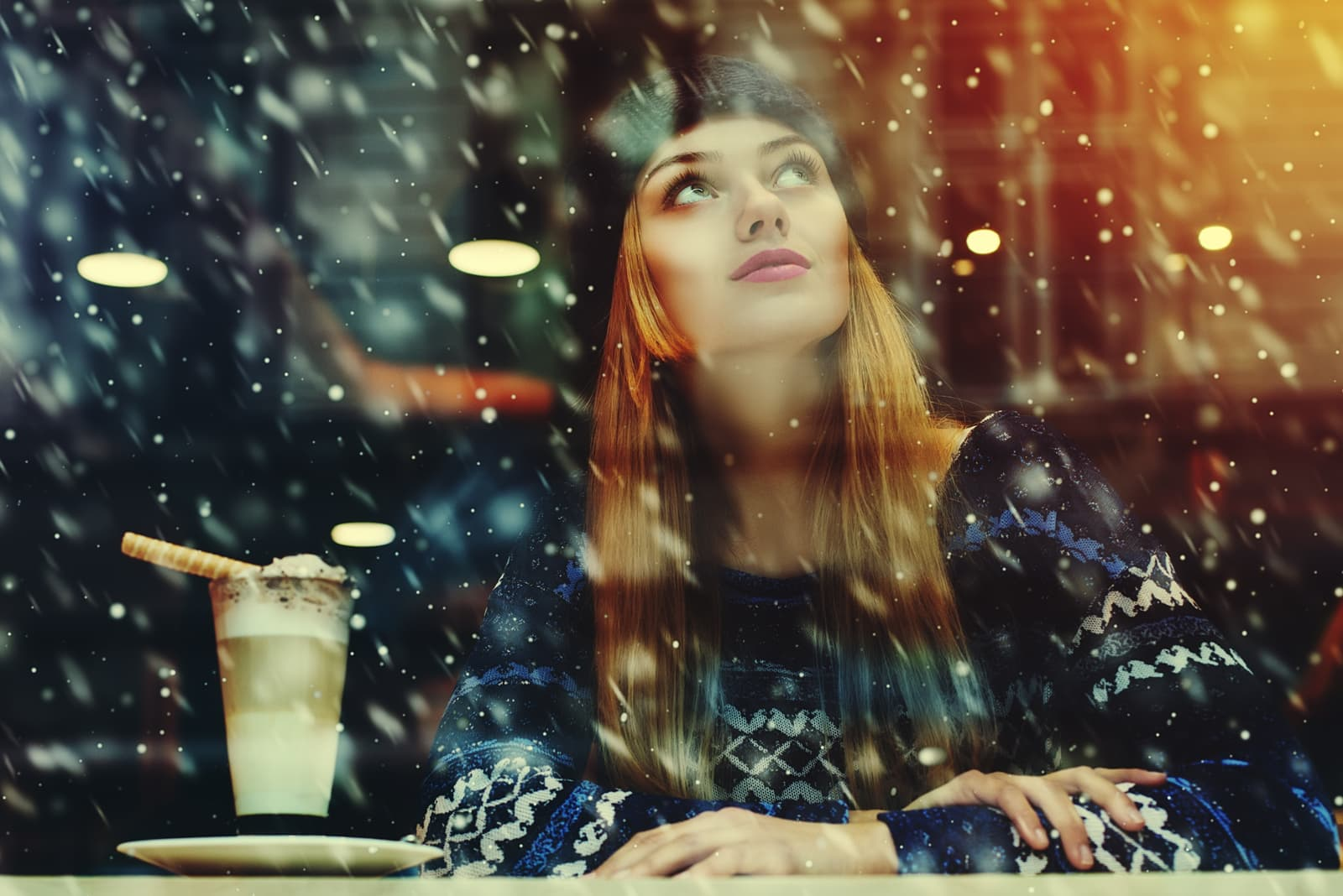 a beautiful girl in a sweater and a cap on her head sits at the bar by the window and watches the snow fall