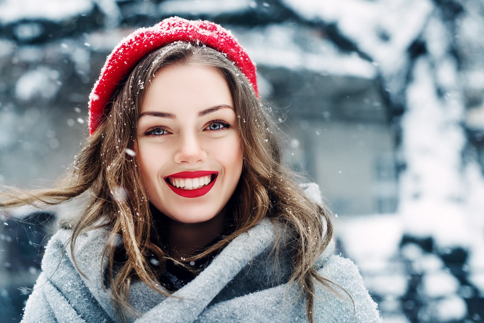 a beautiful smiling brunette with a red cap on her head is standing outside in the snow