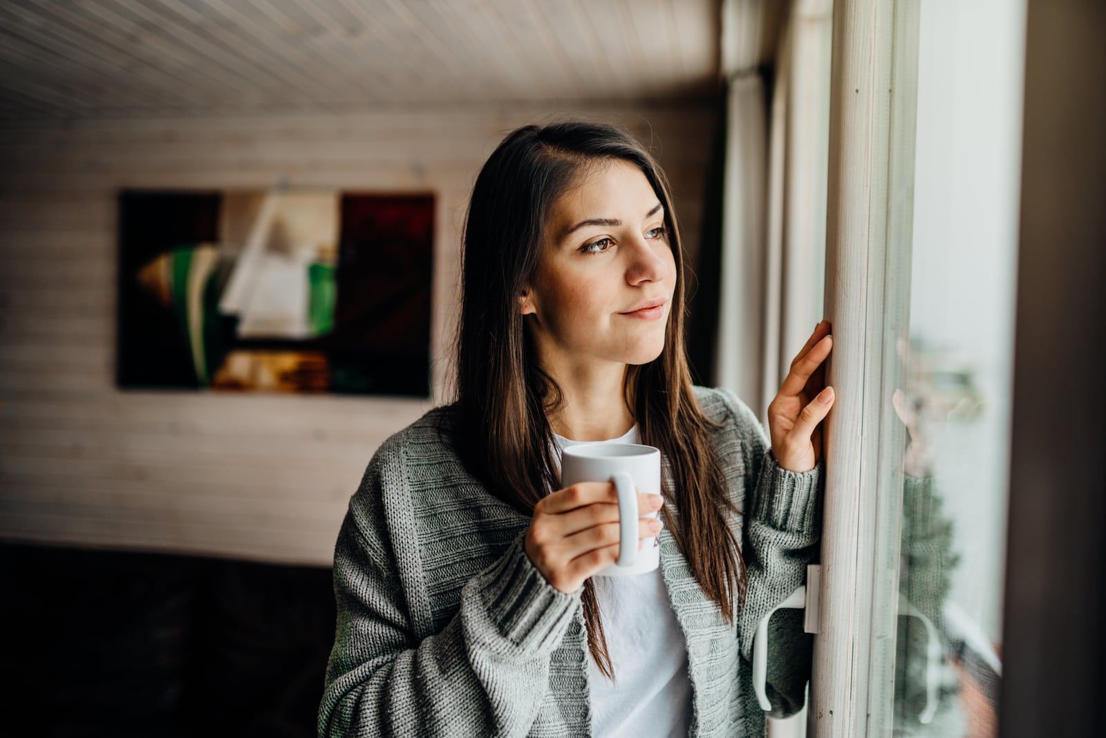 a contented smiling brunette drinks tea and looks out the window
