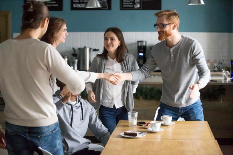 a female greeting with a male in cafe