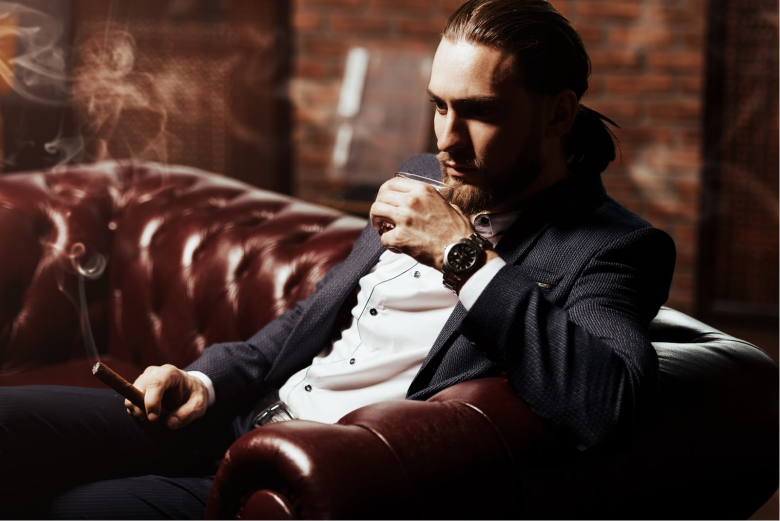 a man sits smoking a cigar and drinking wine