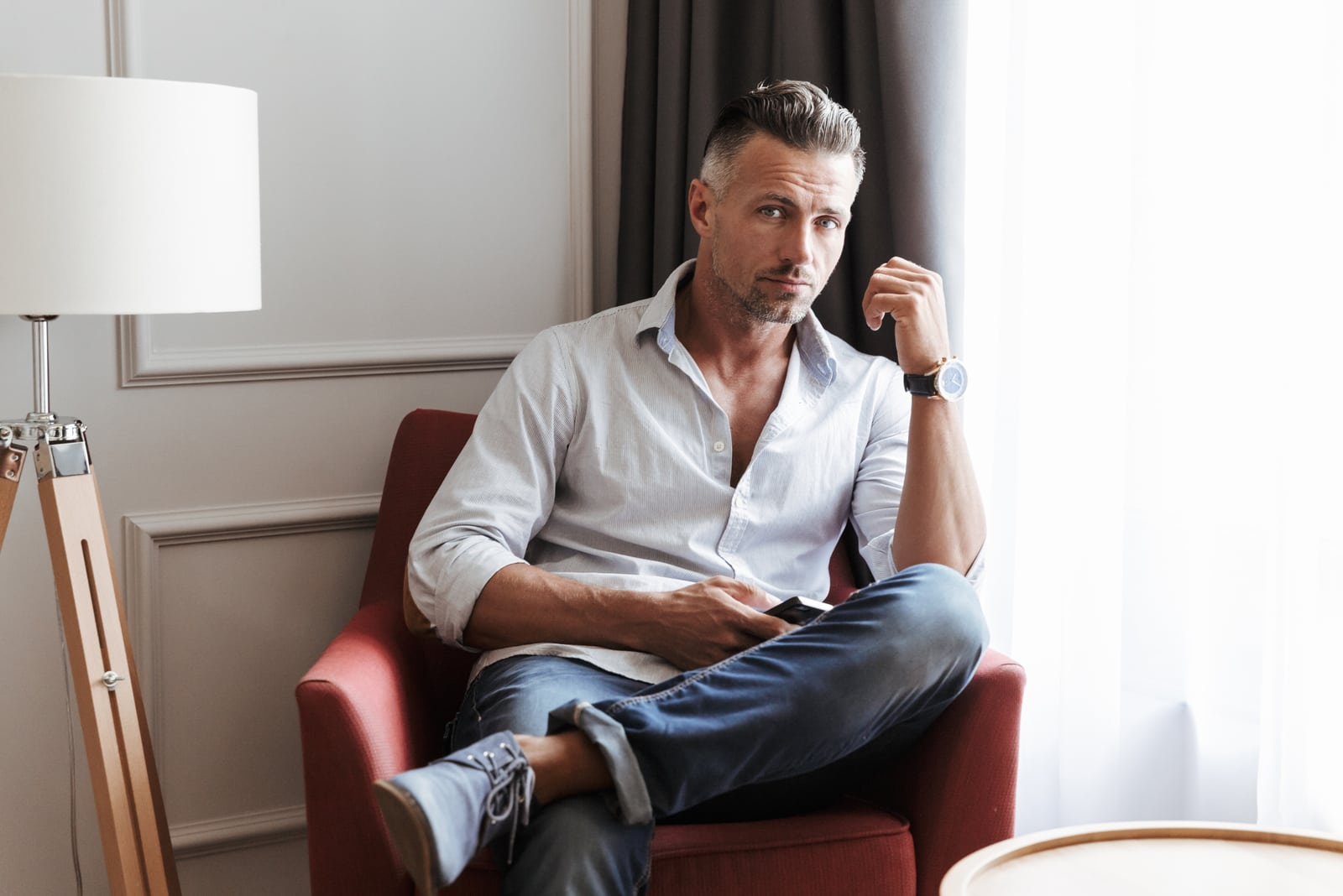 a man sitting in an armchair with a phone in his hand