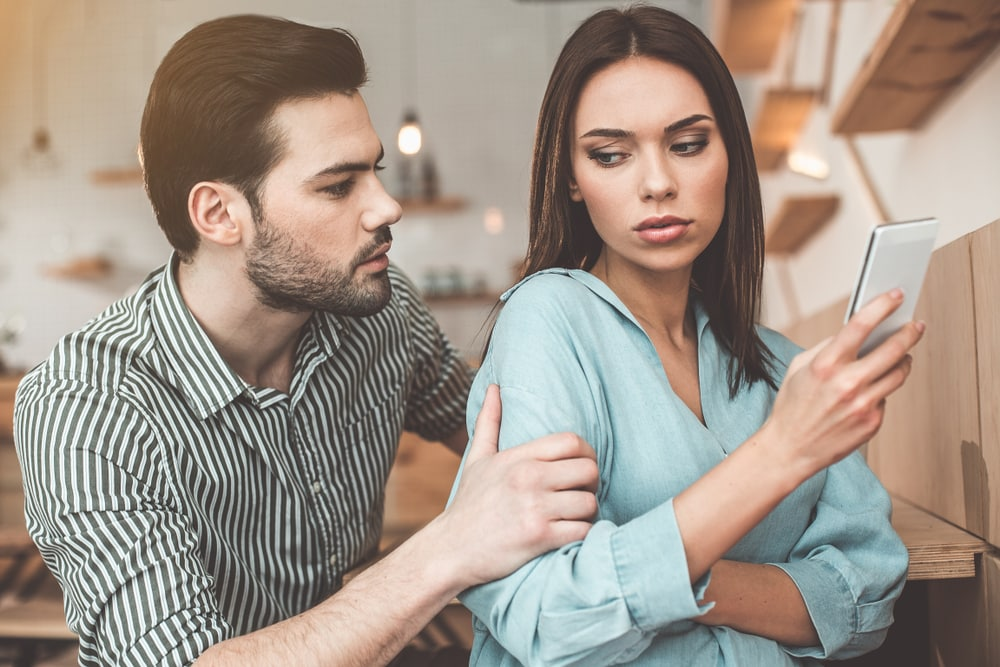 a man touches a woman she holds a phone in her hand
