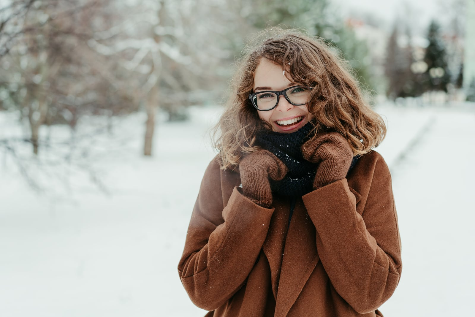 a smiling brunette enjoys a snowy idyll