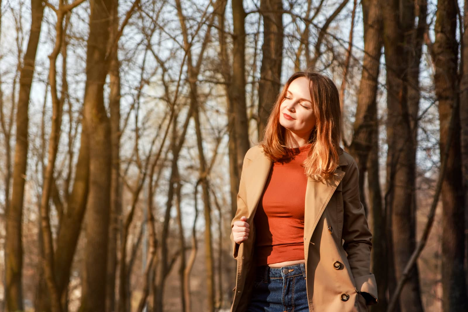 a smiling brunette in the woods stands in a brown coat