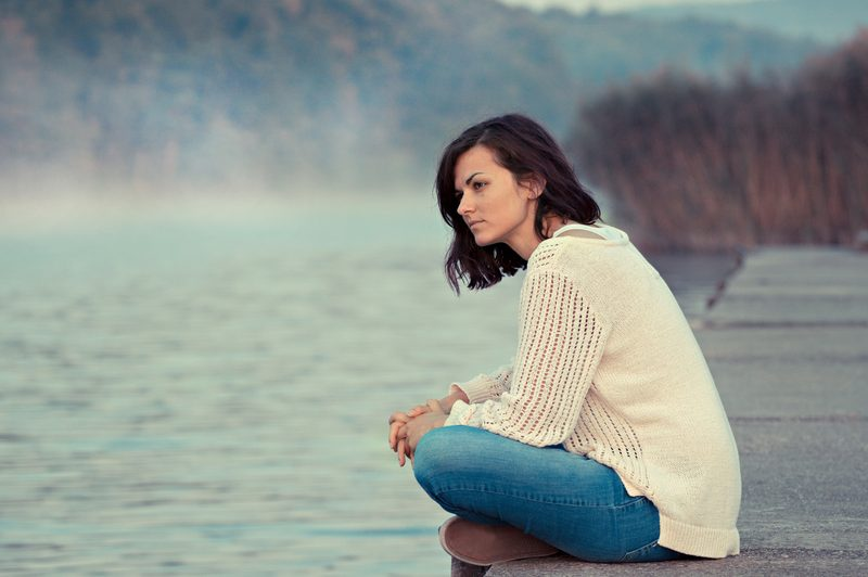 a woman sits by the river on a pier
