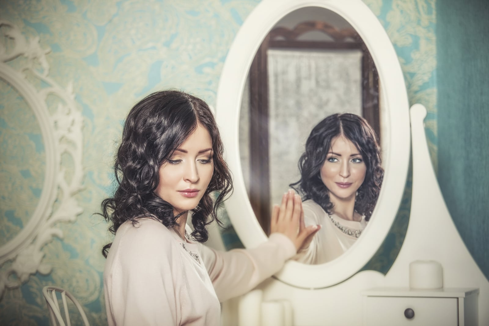 a woman standing next to a mirror