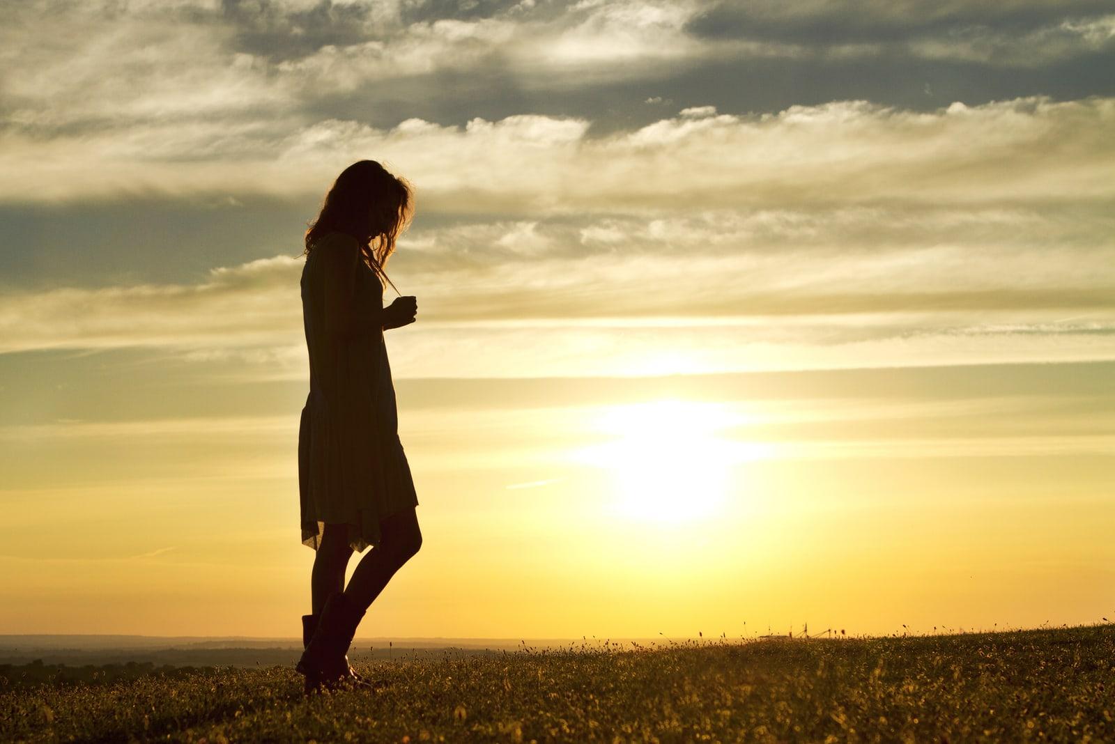 a woman walks through a meadow at sunset