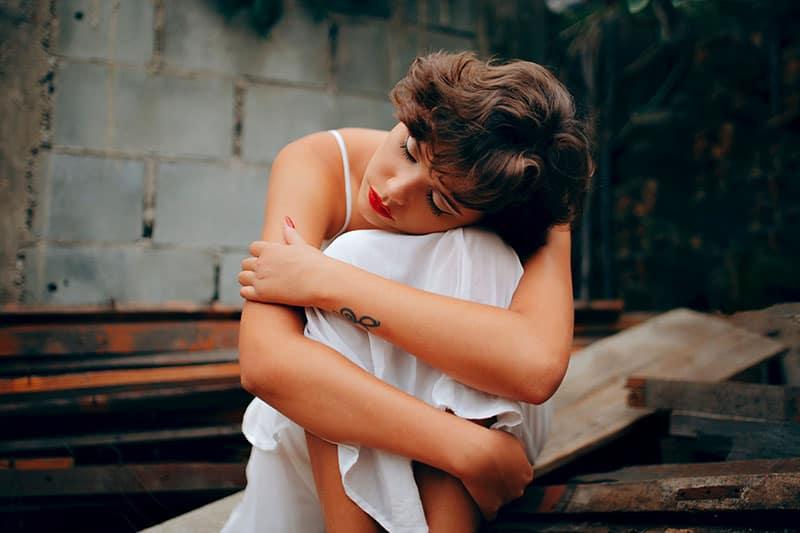 sad woman hugging herself