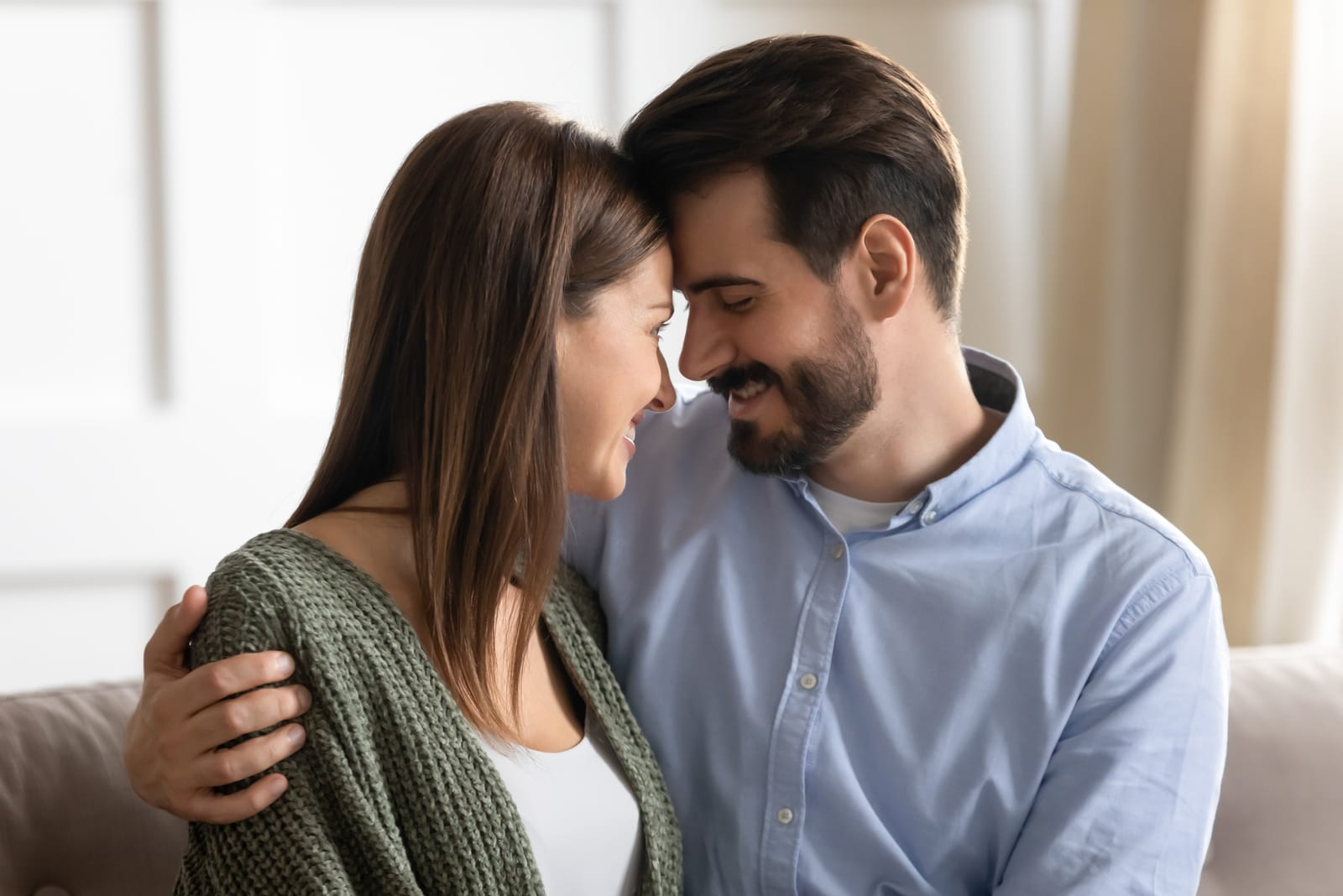 affectionate young man cuddling attractive smiling woman