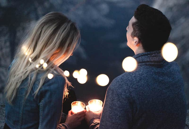 back view of man and woman holding candles