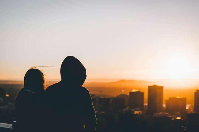 back view of man and woman sitting at looking at city