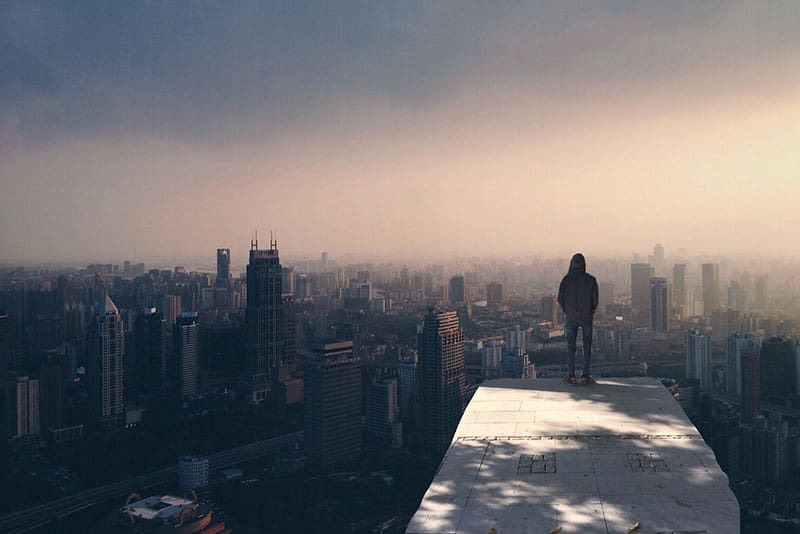 back view of man standing on rooftop with city view