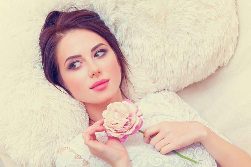 beautiful woman holding a pink rose