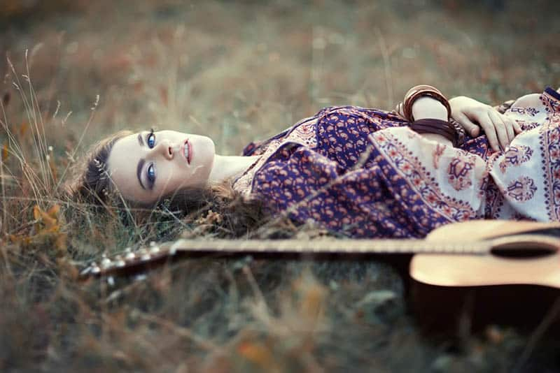 beautiful woman laying on the grass with her guitar