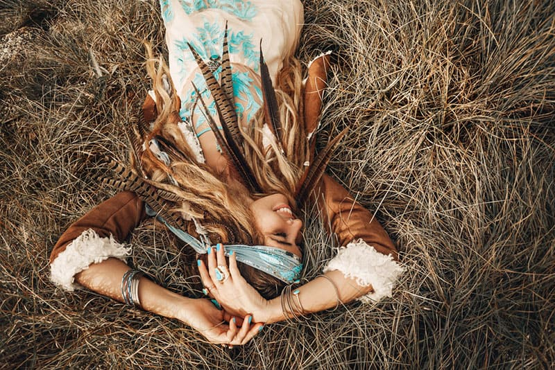 boho girl laying on the grass