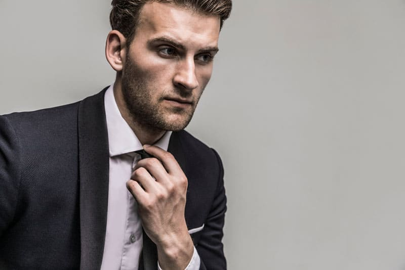close up photo of man in suit making his tie