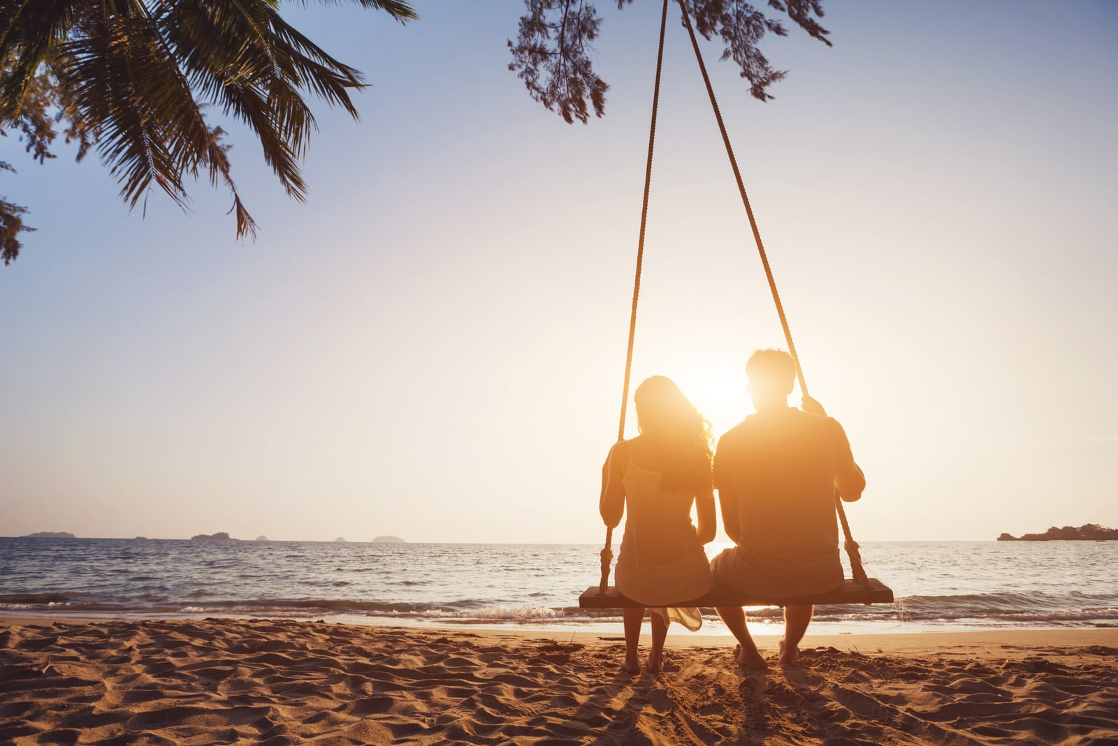 couple in love sitting together on rope swing at sunset beach