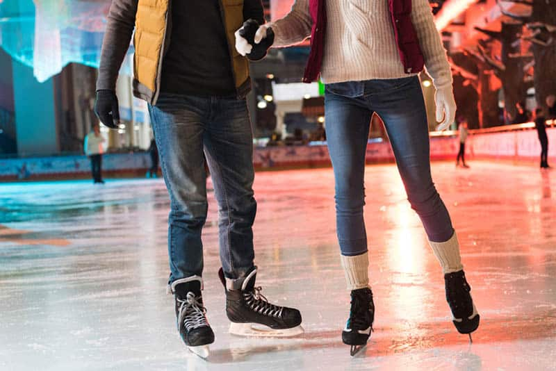 couple in skates holding hands and ice skating on rink