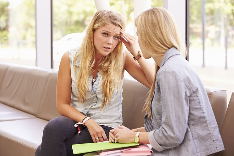 exhausted woman talking with friend
