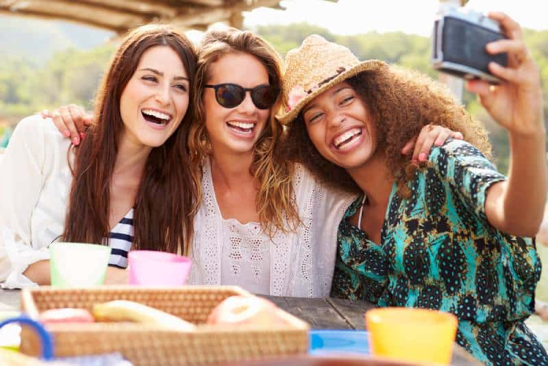 female friends taking selfie during lunch outdoors