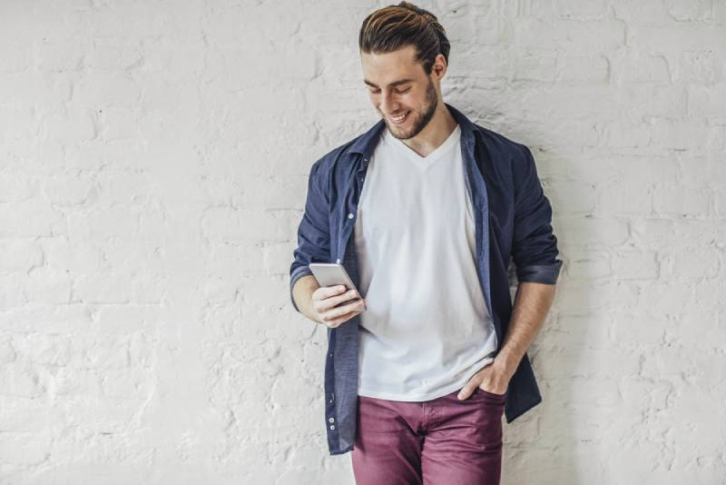 handsome smiling young caucasian man typing on his cell phone.
