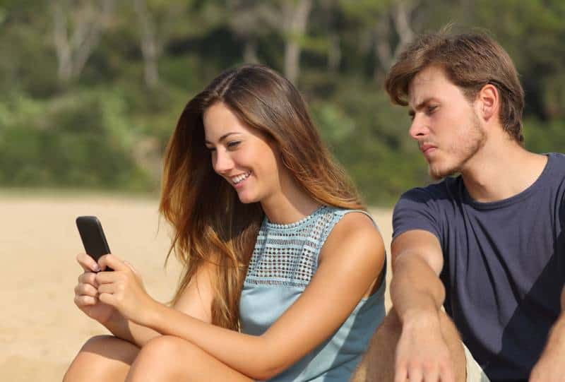 jealous man looking at woman phone