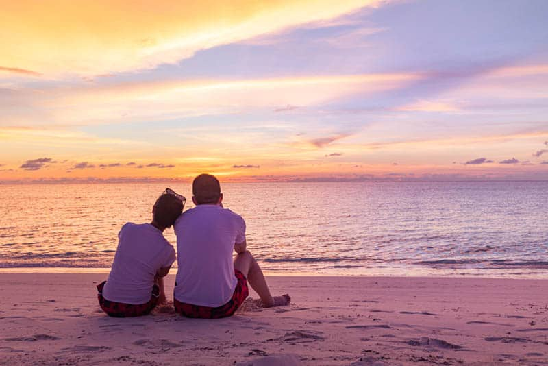 lovely couple sitting on the beach in front of sea