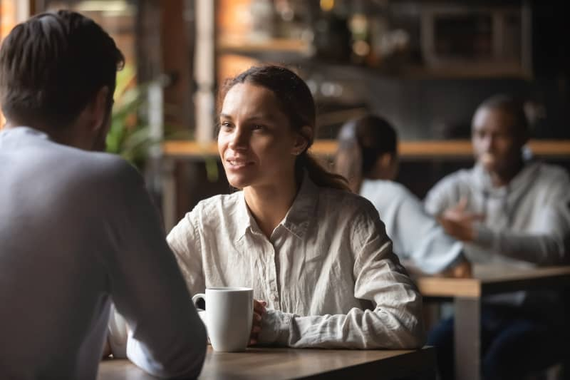 man and woman having a conversation at cafe