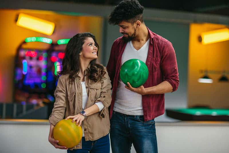 man and woman looking each other and holding bowling ball
