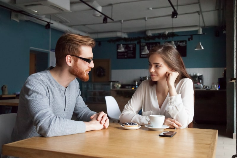 man and woman looking each other and talking in cafe