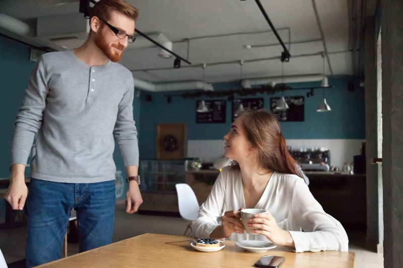 man approaching to woman in cafe