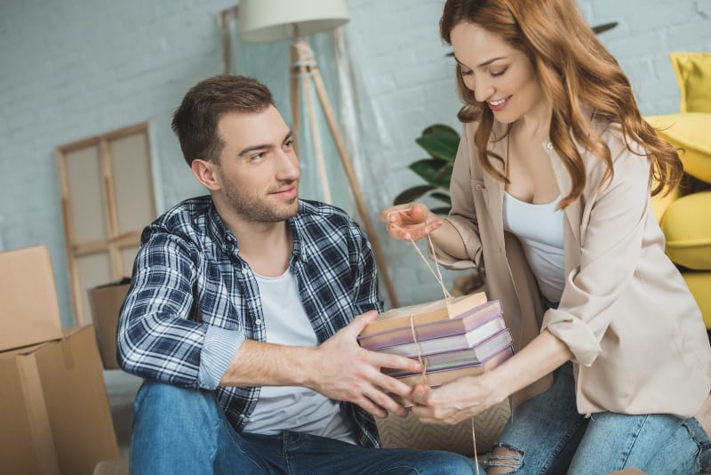 man helping to smiling woman with her books