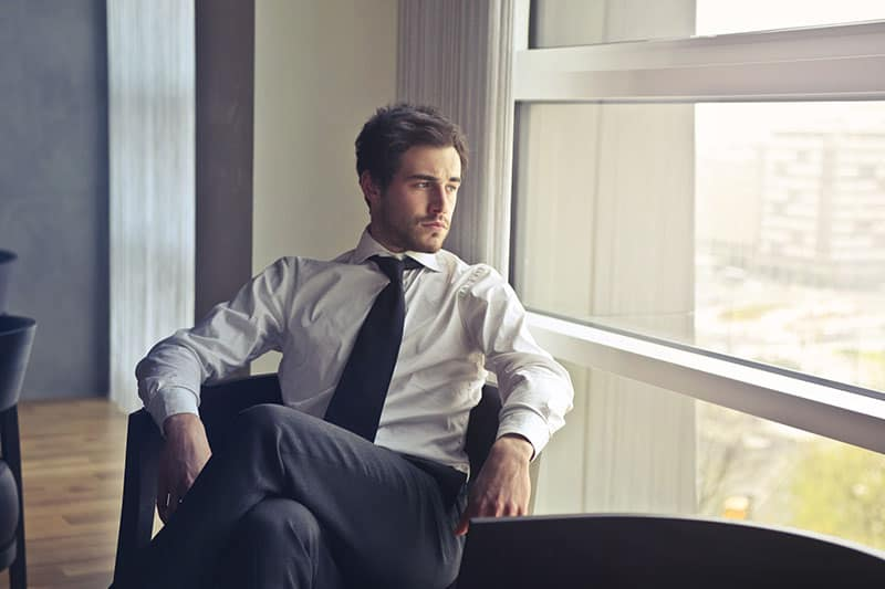 man in shirt and tie sitting beside window