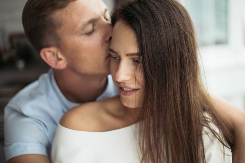 man kissing woman in the head