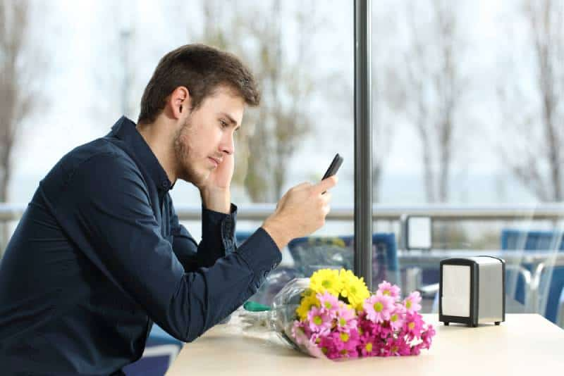 man looking at phone unhappy