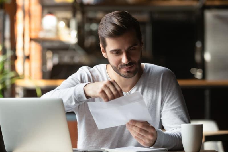 man opening envelope at home