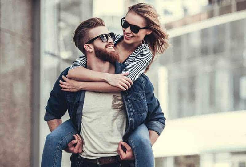 man piggybacking smiling woman outside