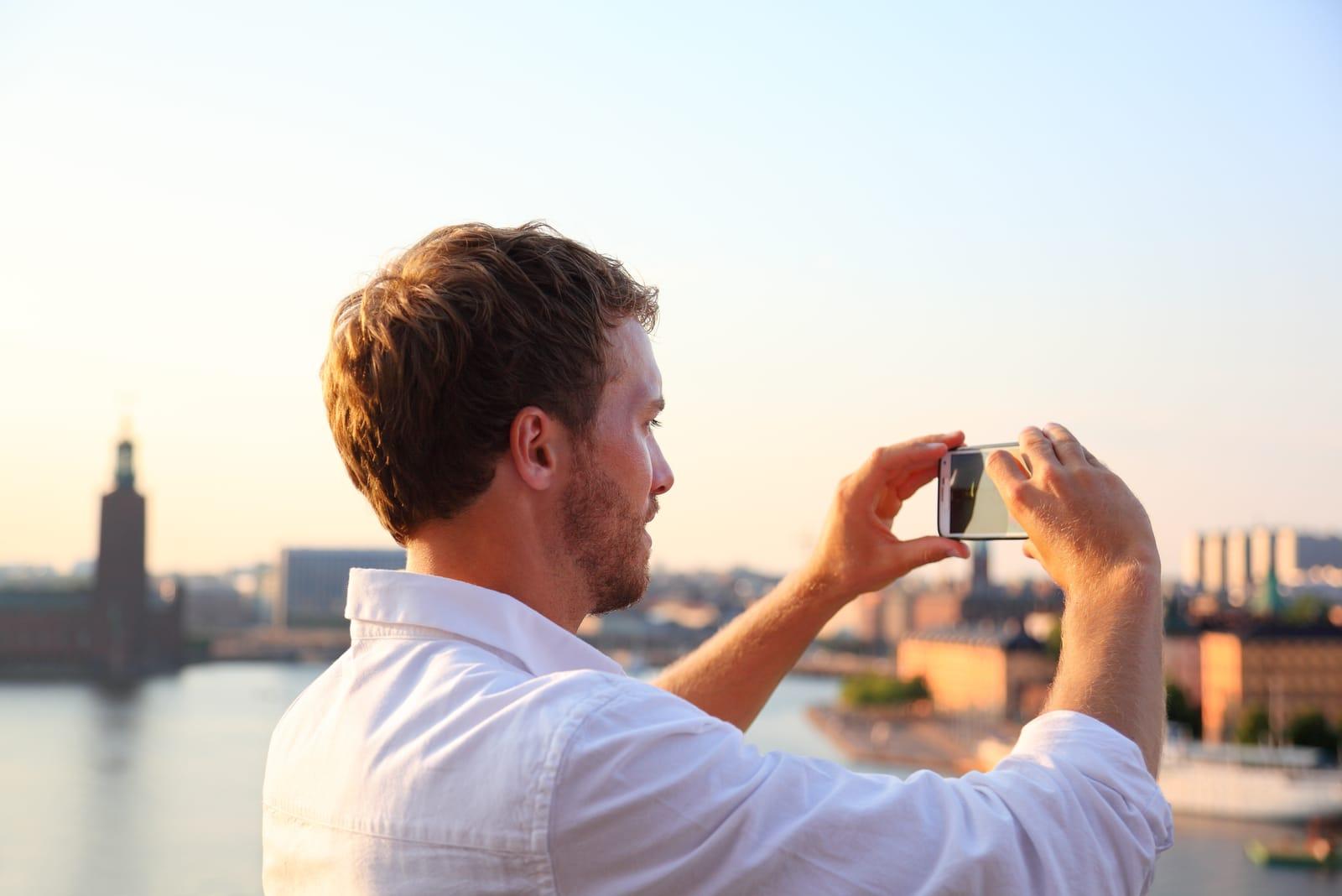 man taking photograph of sunset